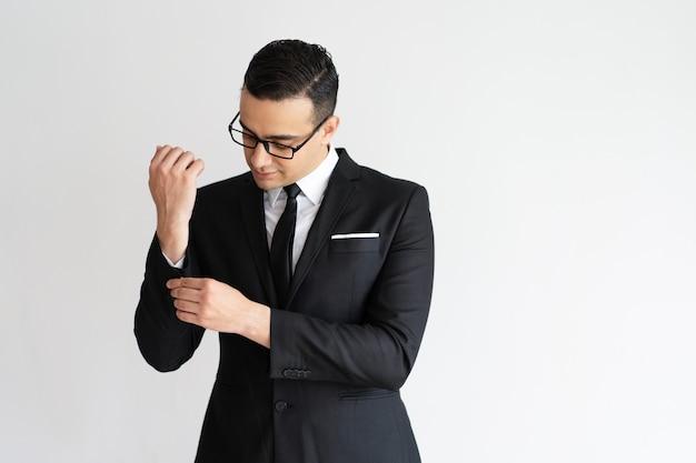 Homem de negócios novo elegante sério que abotoa o punho do revestimento. Foto gratuita