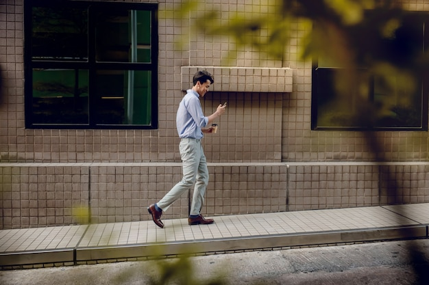 Homem de negócios novo feliz no desgaste ocasional usando ou lendo o telefone celular ao andar pelo edifício urbano. estilo de vida das pessoas modernas. vista lateral. comprimento total Foto Premium