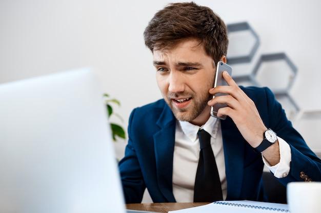 Homem de negócios novo irritado que fala no telefone, fundo do escritório. Foto gratuita