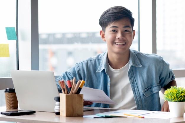 Homem de negócios novo na roupa ocasional que senta-se em sua mesa no escritório. Foto Premium