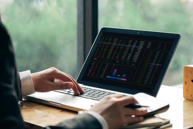 Homem de negócios ou contador trabalhando no computador portátil com documento de negócios e calculadora na mesa de escritório Foto Premium