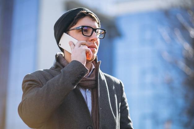 Homem de negócios pelo arranha-céu usando o telefone Foto gratuita