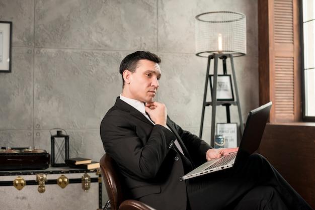 Homem de negócios pensativo com laptop trabalhando em casa Foto gratuita
