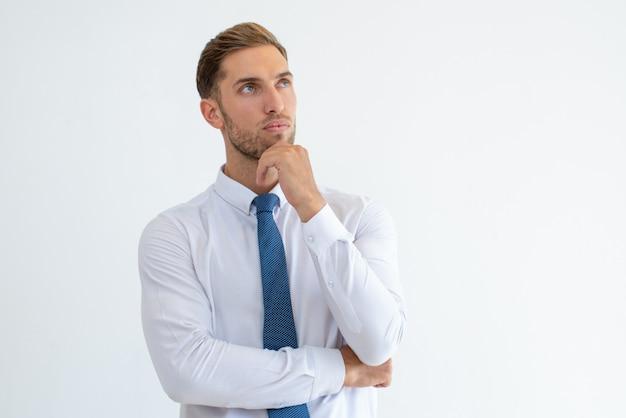 Homem de negócios pensativo tocando o queixo e olhando para longe Foto gratuita