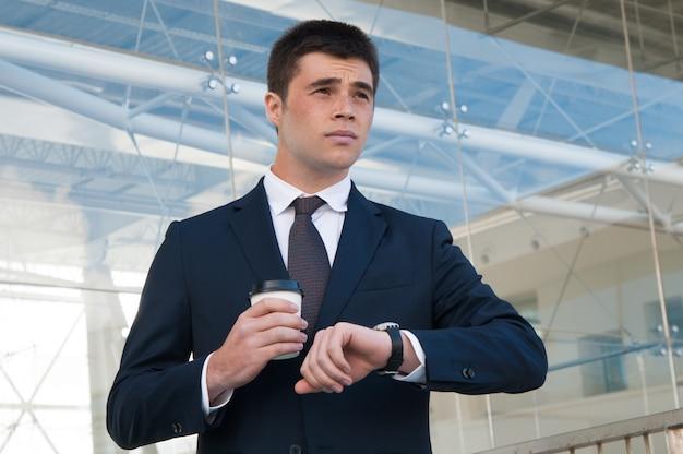 Homem de negócios pensativo, verificando o tempo no relógio ao ar livre Foto gratuita