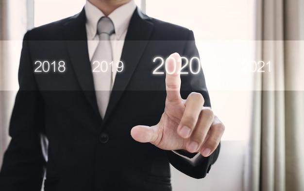 Homem de negócios, pressionando em 2020, ano novo conceito Foto Premium