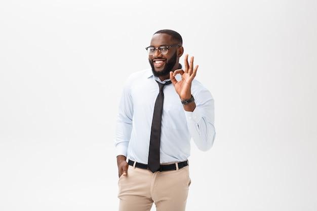 Homem de negócios preto novo que tem o olhar feliz, sorrindo, gesticulando, mostrando o sinal aprovado. Foto Premium