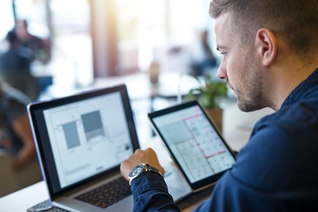 Homem de negócios procurando e analisando projetos em seu laptop e tablet Foto gratuita