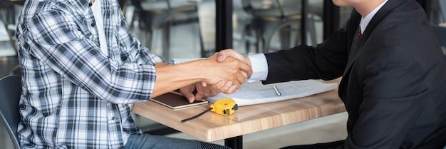Homem de negócios que agita as mãos com o construtor no canteiro de obras, fim acima. Foto Premium