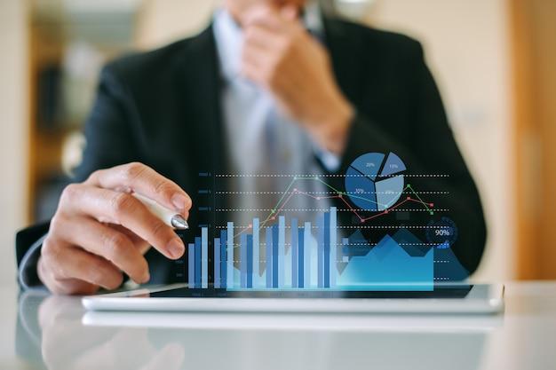Homem de negócios que analisa a empresa financeira trabalhando com gráficos digitais da realidade aumentada. Foto Premium