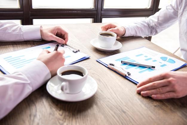 Homem de negócios que analisa gráficos com xícara de café. Foto Premium