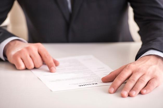 Homem de negócios que analisa o resumo na mesa no escritório. Foto Premium