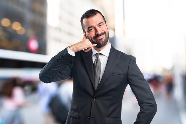 Homem de negócios que faz o gesto do telefone em um fundo sem foco Foto Premium