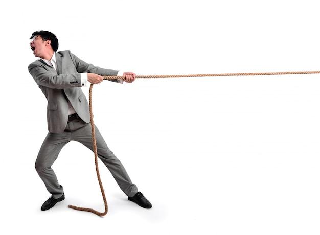 Homem de negócios que puxa em uma corda Foto gratuita