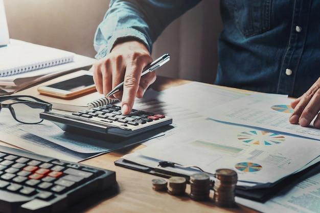 Homem de negócios que usa a calculadora com a pena de terra arrendada da mão que trabalha no escritório. Foto Premium