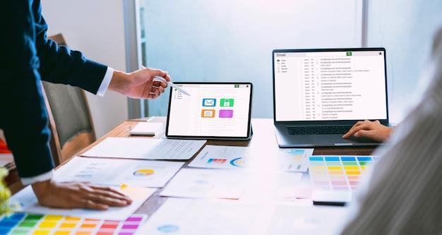 Homem de negócios que usa a comunicação da conexão da tela do email da leitura do portátil e da tabuleta. Foto Premium