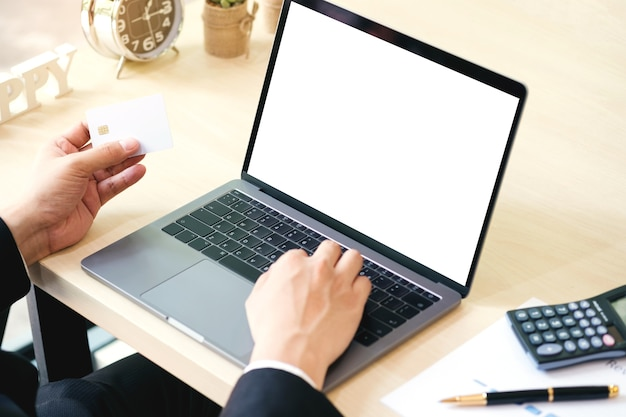 Homem de negócios que usa o portátil com a tela vazia na mesa com crédito de crédito para comprar. Foto Premium