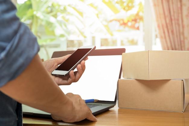 Homem de negócios que verifica o iventory no telefone celular com o pacote e o portátil na tabela. Foto Premium