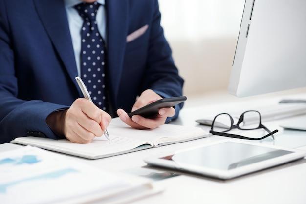 Homem de negócios recortado, fazendo anotações de seu calendário de smartphone para o organizador Foto gratuita