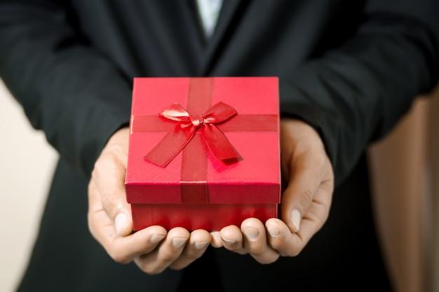 Homem de negócios segura caixa de presente vermelha nas mãos. Foto Premium