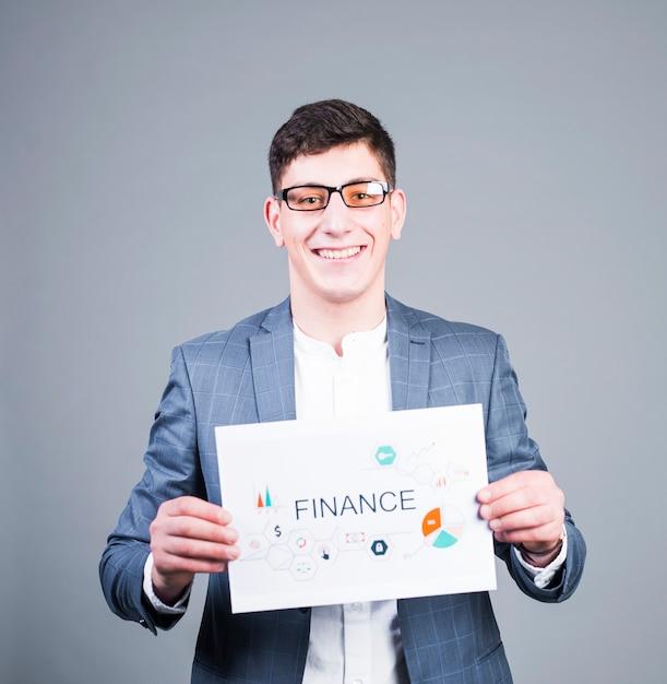Homem de negócios, segurando o papel com inscrição de finanças e sorrindo Foto gratuita