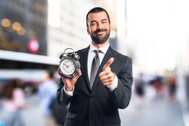 Homem de negócios segurando relógio vintage em fundo sem foco Foto Premium