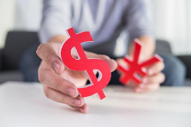 Homem de negócios segurando sinal de dólar e sinal cny Foto gratuita