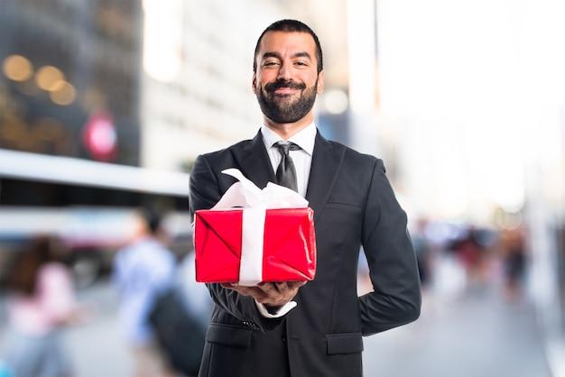Homem de negócios segurando um presente em um fundo sem foco Foto Premium