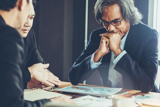 Homem de negócios sênior como chefe na reunião e discutir a situação no mercado de ações. Foto Premium