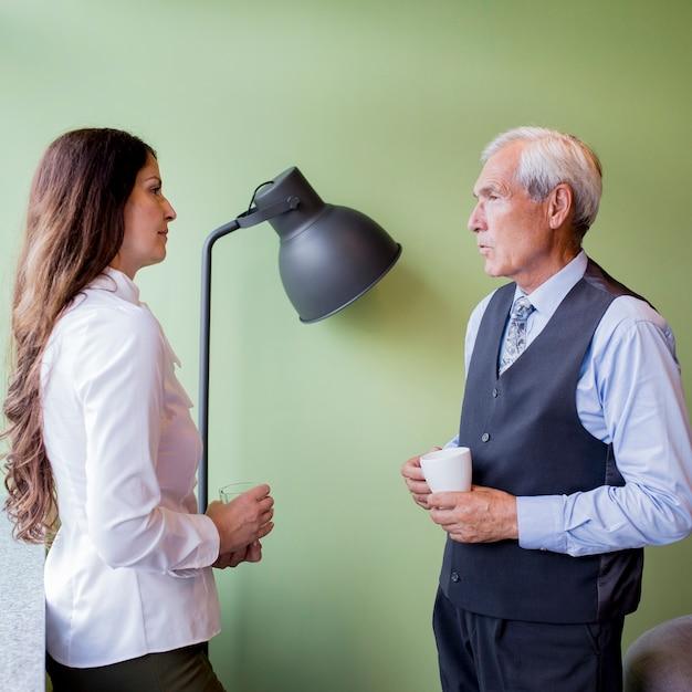 Homem de negócios sênior e empresária madura interagindo durante uma pausa Foto gratuita