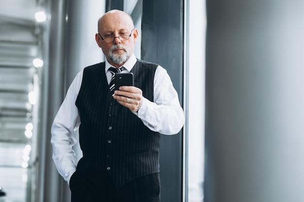Homem de negócios sênior falando ao telefone no escritório Foto gratuita