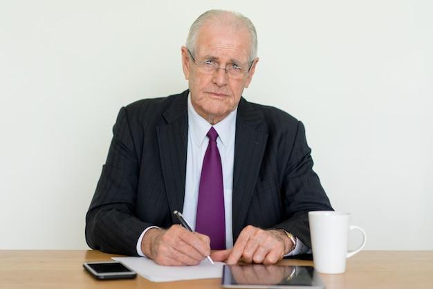 Homem de negócios sênior pensativo olhando para a câmera, escrevendo e usando o computador tablet Foto Premium