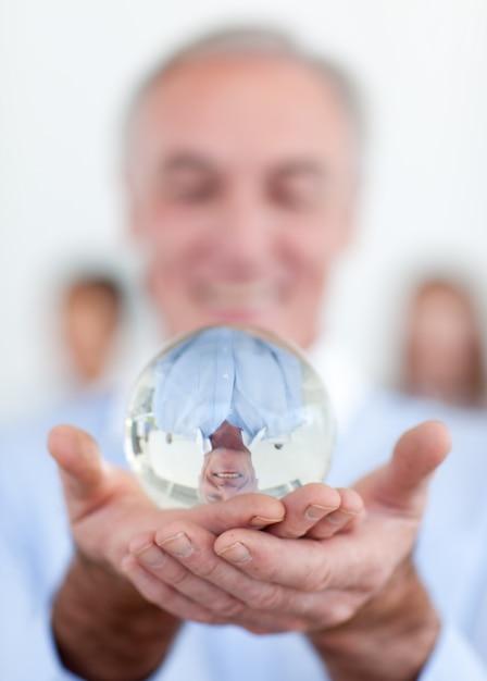 Homem de negócios sênior segurando uma bola de cristal Foto Premium