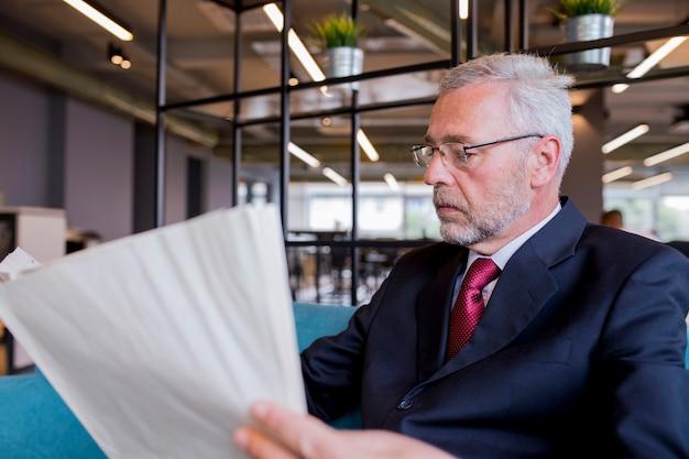 Homem de negócios sênior, sentado lendo jornal no escritório Foto gratuita
