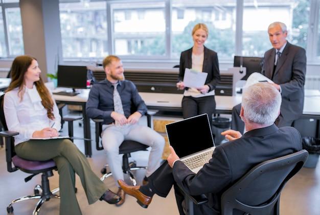 Homem de negócios sênior sentado na cadeira com laptop sentado na frente de sua equipe no escritório Foto gratuita