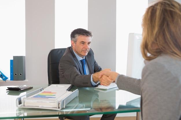 Homem de negócios sério, apertando a mão do entrevistado Foto Premium