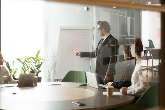 Homem de negócios sério apresentando objetivos de negócio da empresa para os colegas Foto gratuita