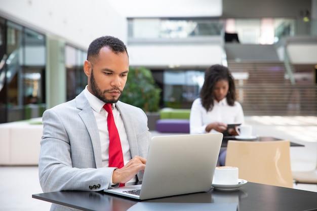 Homem de negócios sério bebendo café e trabalhando Foto gratuita