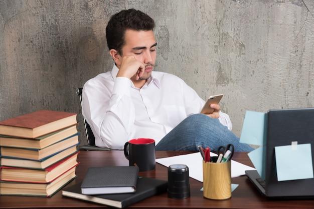 Homem de negócios sério brincando com o telefone na mesa do escritório. Foto gratuita