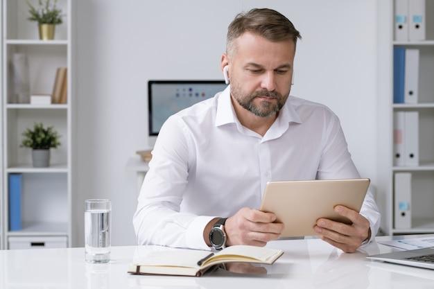 Homem de negócios sério com airpods olhando para a tela do touchpad enquanto assiste a um vídeo de treinamento, conferência ou webinar online Foto Premium
