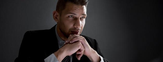 Homem de negócios sério com as mãos no queixo no fundo escuro banner Foto Premium
