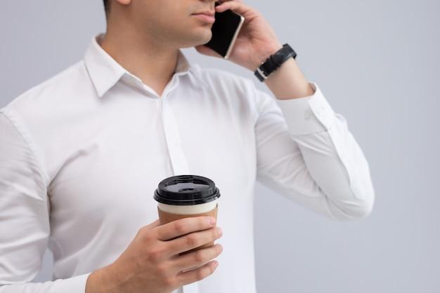 Homem de negócios sério com café para viagem falando no celular Foto gratuita