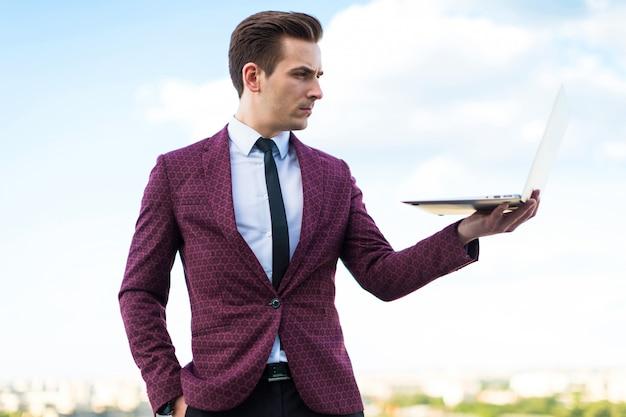 Homem de negócios sério de terno vermelho e camisa com gravata fica no telhado com o laptop Foto Premium