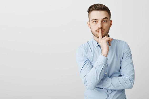 Homem de negócios sério dizendo shh, fazendo sinal de silêncio, precisa de silêncio para pensar Foto gratuita