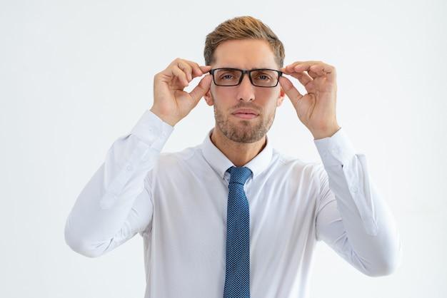 Homem de negócios sério olhando a câmera através de óculos Foto gratuita