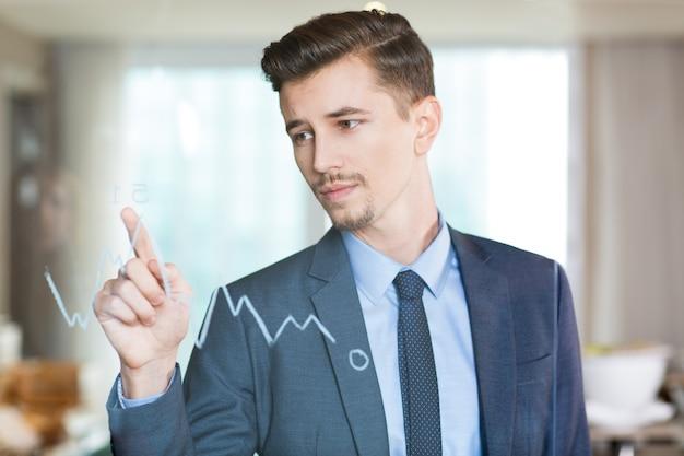 Homem de negócios sério que aponta ao gráfico no vidro Foto gratuita