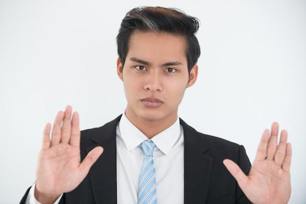 Homem de negócios sério que mostra um gesto de rendição Foto gratuita