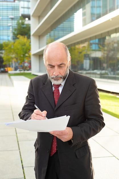 Homem de negócios sério tomando notas na rua Foto gratuita