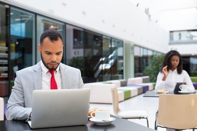 Homem de negócios sério trabalhando no laptop enquanto bebe café Foto gratuita