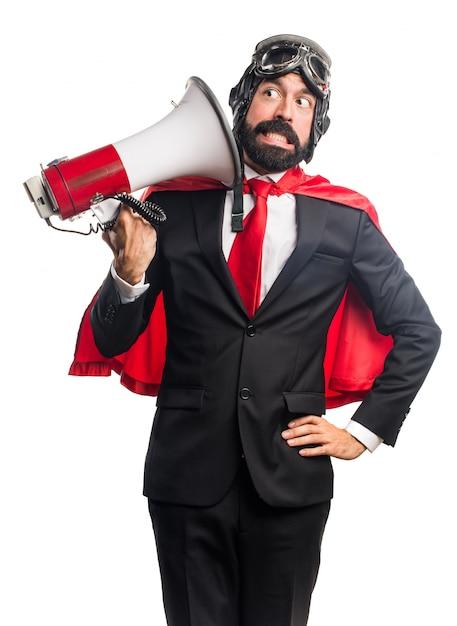 Homem de negócios super-herói gritando por megafone Foto gratuita